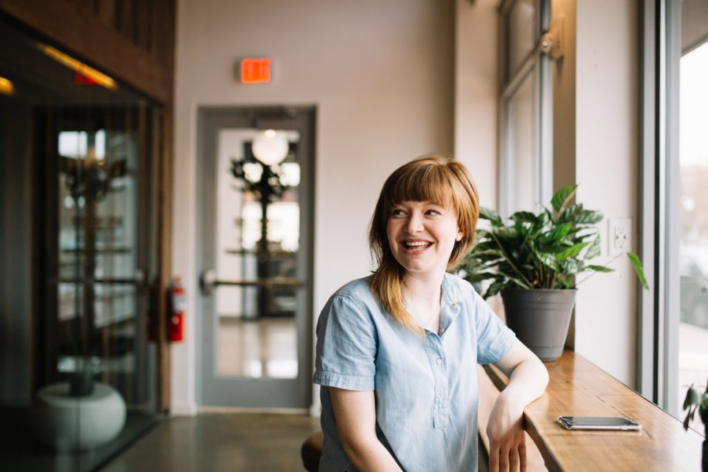 Sympathische, lächelnde Frau mit grüner Pflanze in Videokonferenz