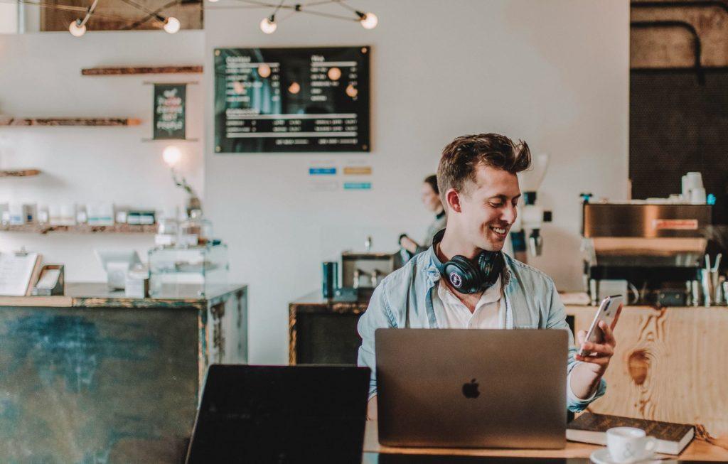 Mann am Laptop und Handy in einer Videokonferenz